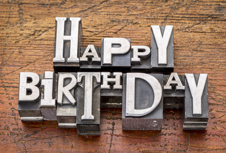 Happy Birthday greetings  in vintage metal type printing blocks over grunge wood