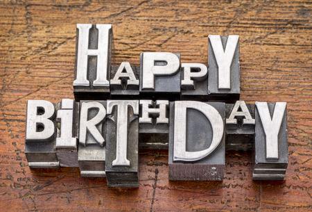 letterpress type: Happy Birthday greetings  in vintage metal type printing blocks over grunge wood