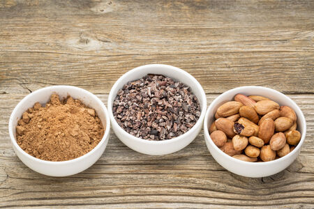 nib: cacao beans, nibs and powder in white ceramic bowls against grained wood