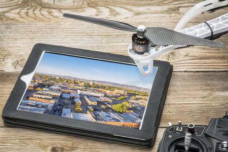 無人空中写真コンセプト - ドローン ローターとラジオ コントロール機とデジタル タブレットにダウンタウン フォート コリンズの空中写真を確認