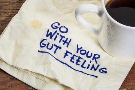 tovagliolo: andare con il vostro istinto - consiglio o promemoria motivazionale su un tovagliolo con una tazza di caff� espresso Archivio Fotografico