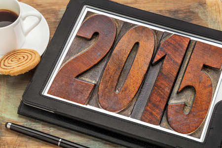 2015  - New Year concept  - isolated text in vintage wood type printing blocks on a digital tablet with a cup of coffee photo