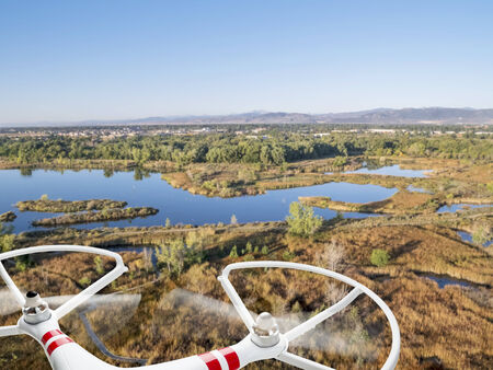 rotating propellers of a helicopter drone flying over lake and swamp landscape in northern Colorado