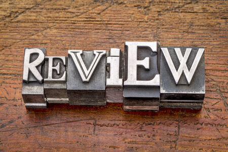 commentary: review word in mixed vintage metal type printing blocks over grunge wood Stock Photo