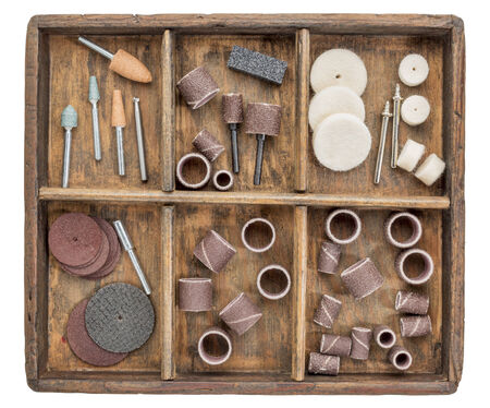 rotary tool accessories in wooden rustic box isolated on white Stock Photo