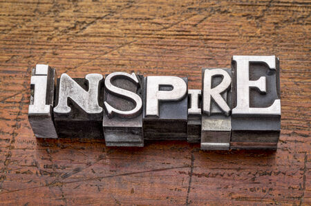 role model: inspire word in mixed vintage metal type printing blocks over grunge wood