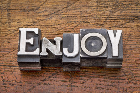enjoy  word in mixed vintage metal type printing blocks over grunge wood photo