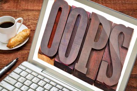 internet concept - Oeps uitroepteken word in vintage houten boekdruk blokken op laptop scherm Stockfoto
