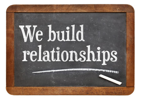 We build relationships - white chalk text on a vintage slate blackboard Stock Photo
