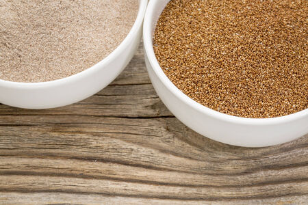 teff grain and flour in small ceramic bowls against grained wood background Stok Fotoğraf