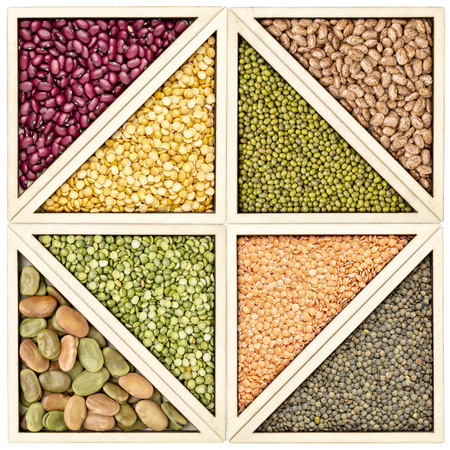 a variety of beans, pea and lentils in a wooden tray inspired by tangram puzzle Stock Photo