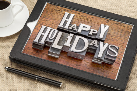 holidays: Happy Holidays greetings  in vintage metal type printing blocks on a digital tablet with a cup of coffee
