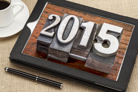 2015  - New Year concept  - number in vintage metal type printing blocks on a digital tablet with a cup of coffee photo