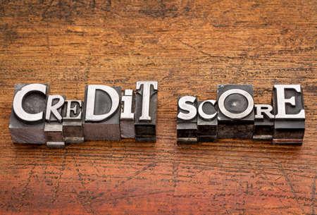 credit score: credit score text in mixed vintage metal type printing blocks over grunge wood