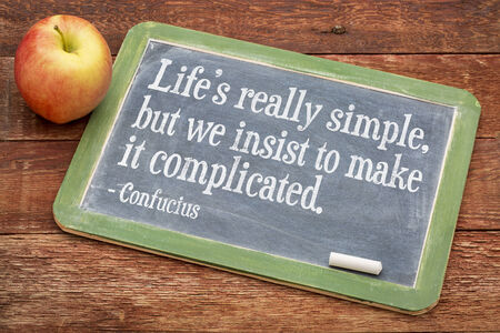insist: Life is really simply, but we insist to complicate it - a wisdom quote by Confucius on a slate blackboard against red barn wood Stock Photo