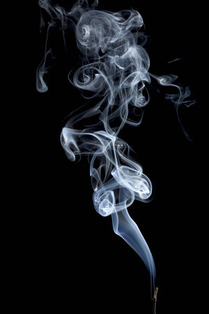 delicate smoke plume from a burning incense stick photo