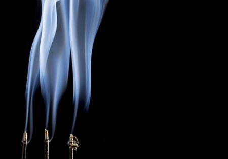 delicate smoke plumes from burning incense sticks with a copy space 版權商用圖片