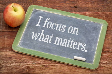 affirmation: I focus on what matters - positive affirmation words on a slate blackboard against red barn wood