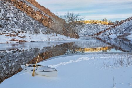 horsetooth reservoir: decked expedition canoe on icy shore  of Horsetooth Reservoir near Fort Collins in northern Colorado, winter scenery