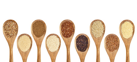a variety of gluten free grains (buckwheat, amaranth, brown rice, millet, sorghum, teff, black, red and white quinoa) on wooden spoons isolated on white Imagens - 35089322