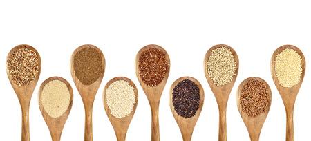 Een verscheidenheid aan glutenvrije granen (boekweit, amarant, bruine rijst, gierst, sorghum, teff, zwart, rood en wit quinoa) op houten lepels geïsoleerd op wit Stockfoto - 35089322