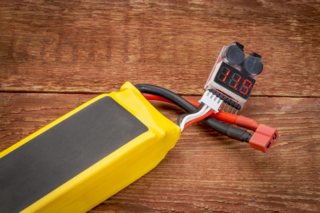 abbreviated: Lithium-ion polymer rechargeable battery (abbreviated as LiPo, LIP, Li-poly) with a digital LED voltage meter connected to a balance plug. Stock Photo