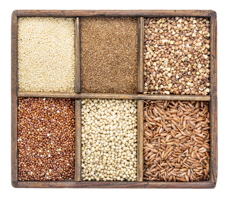 red quinoa: a variety of gluten free grains (buckwheat, amaranth, brown rice, millet, sorghum, teff,  red quinoa) in a rustic wooden box isolated on white