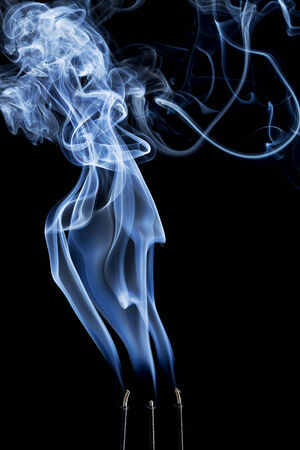 dispersion: delicate smoke plume and swirls from  burning three incense sticks Stock Photo