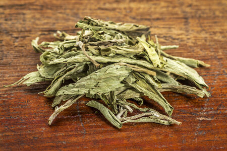 substitute: pile of stevia dried leaves against grunge wood -  natural sweetener, sugar substitute Stock Photo