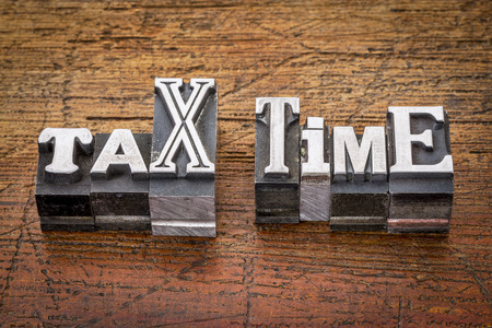 tax time - financial concept - words in mixed vintage metal type printing blocks over grunge wood photo