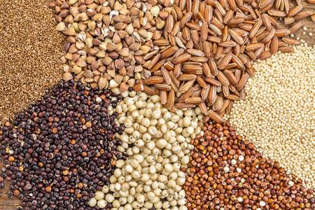 sorgo: una variedad de cereales sin gluten (trigo sarraceno, amaranto, arroz integral, mijo, sorgo, teff, quinua roja) i- vista superior Foto de archivo