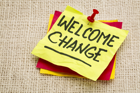 welcome change  - advice on a sticky note against burlap canvas