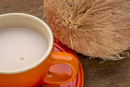 stoneware: a stoneware cup of coconut milk with a coconut against wood background