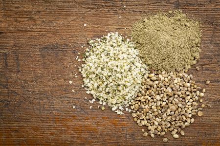 hemp hemp seed: hemp seed, hearts and protein powder - small piles on a grunge wood - top view