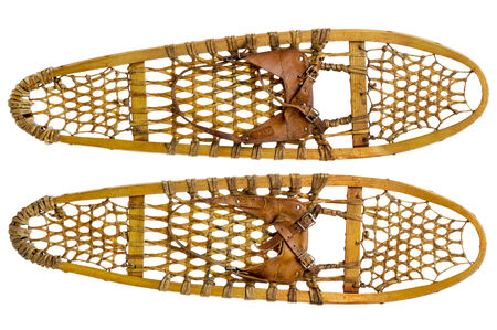 white paw: a pair of vintage wooden Bear Paw snowshoes with leather binding isolated on white