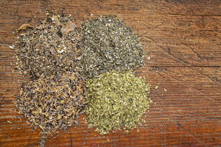 background of four seaweed dietary supplements (Irish moss, wakame, sea lettuce and bladderwrack) on a grunge wood