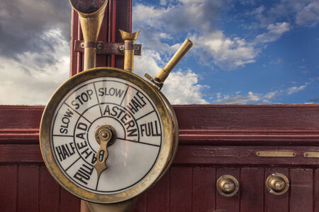 wheelhouse: engine controls (telegraph) on a vintage ship bridge with a stormy sky in background