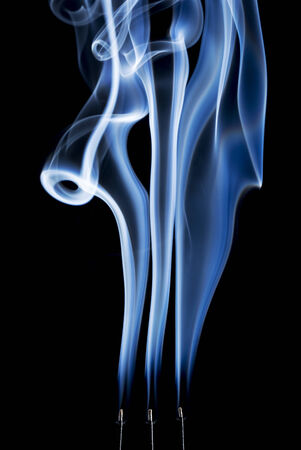 delicate smoke plumes, puffs and eddies  from  burning incense sticks photo
