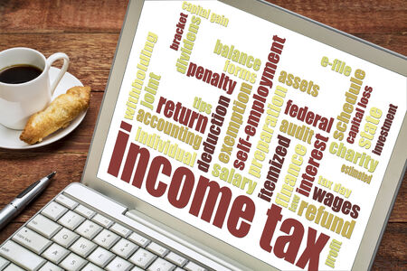 income tax word cloud on a laptop screen with a cup of coffee Stock Photo