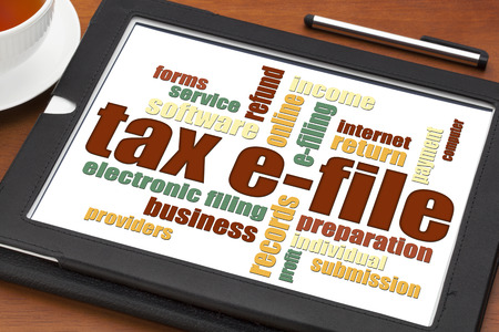 income tax: tax electronic filing concept - a word cloud on a digital tablet with a cup of tea Stock Photo