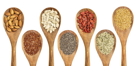 flax seed: superfood abstract - isolated wooden spoons with almonds, red quinoa grain, pumpkin seeds, chia seeds, goji berry, hemp seed hearts, and golden flax seed