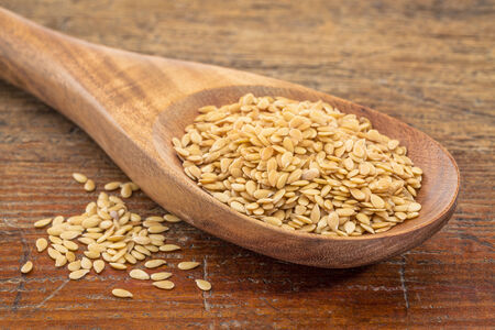 gold flax seeds on a wooden spoon against a grunge wood Фото со стока