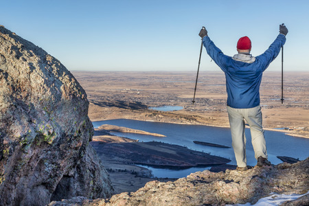 horsetooth rock: a male hiker with trekking poles overlooking Horsetooth Reservoir from Arthurs Rock near Fort Collins, Colorado, a typical winter scenery without snow Stock Photo