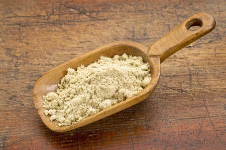a rustic scoop of rice bran against grunge wood Stok Fotoğraf
