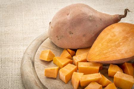 camote: dulce patata cortada en dados y sobre una tabla de cortar
