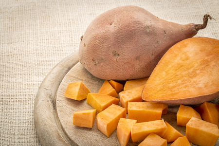 sweet: sweet potato cut and diced on a cutting board