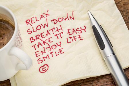 napkin: concepto de reducción del estrés - relajarse, reducir la velocidad, la respiración, tómalo con calma, disfrutar de la vida, la sonrisa de escritura a mano en una servilleta con una taza de café