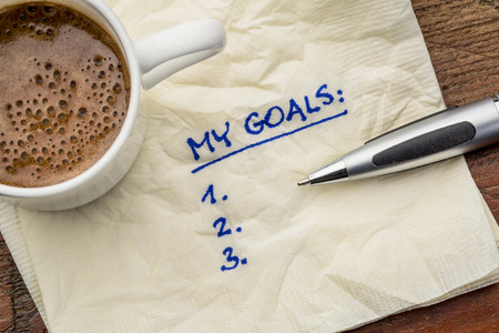 my goals list on a napkin with cup of coffee