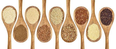 a variety of gluten free grains (buckwheat, amaranth, brown rice, millet, sorghum, teff, black, red and white quinoa) on wooden spoons isolated on white