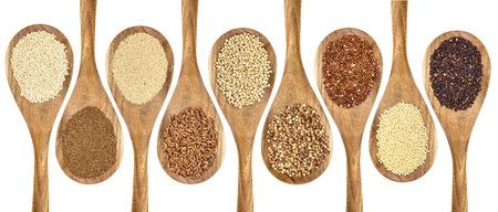 sorgo: una variedad de cereales sin gluten (trigo sarraceno, amaranto, arroz integral, mijo, sorgo, teff, quinua negro, rojo y blanco) de cucharas de madera aislada en blanco Foto de archivo
